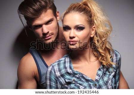 smiling young casual couple looking at the camera in studio