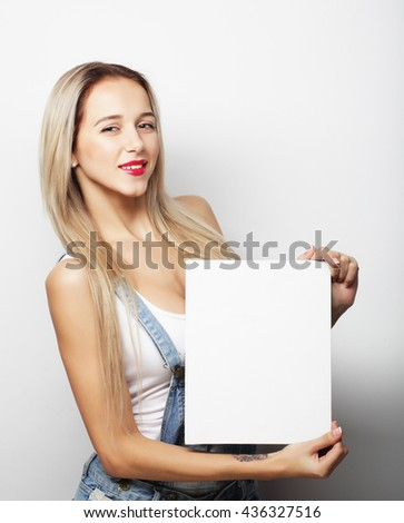 Smiling young casual style woman showing blank signboard, over white background isolated