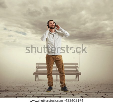 Smiling young Caucasian bearded man in casual clothes and headphones is standing in virtual reality visualization of cloudy sky and lonely street with paving, street lamps and bench - stock photo