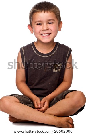 Smiling young caucasian boy sitting with his legs crossed on a white background - stock photo