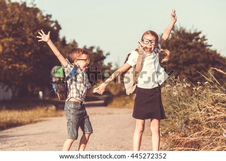 Smiling young  children in a  uniform jumping on the road at the day time. Concept of the kids are ready to go to school. - stock photo