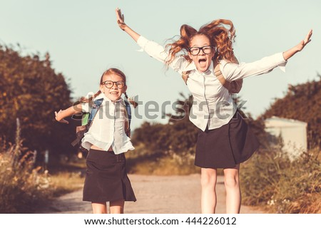 Smiling young  children in a  uniform jumping on the road in the park at the day time. Concept of the girls are ready to go to school. - stock photo