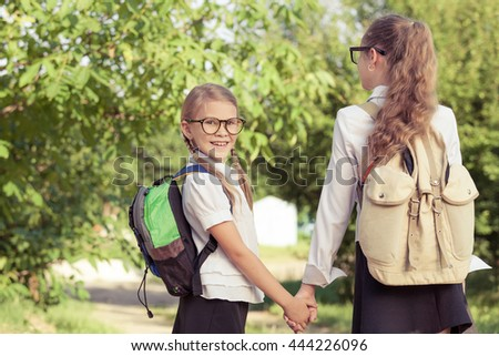 Smiling young  children in a  uniform standing against a tree in the park at the day time. Concept of the girls are ready to go to school. - stock photo