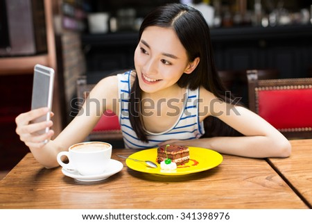 smiling young chinese woman holding phone and coffee self-timer - stock photo