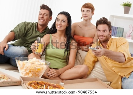 Smiling young companionship watching tv together, having pizza and chips.? - stock photo
