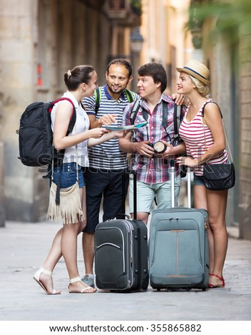 Smiling young company of impressed travelers during city walking - stock photo