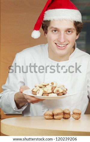 Smiling young confectioner in santa hat holds plate with cookies and cakes