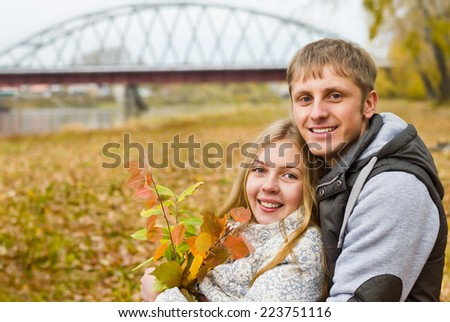 Smiling young couple at river in autumn - stock photo