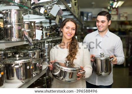 Smiling young couple choosing new pans in kitchenware section in supermarket . Focus on woman