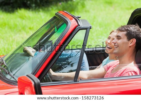 Smiling young couple having a ride in red cabriolet on a sunny day - stock photo