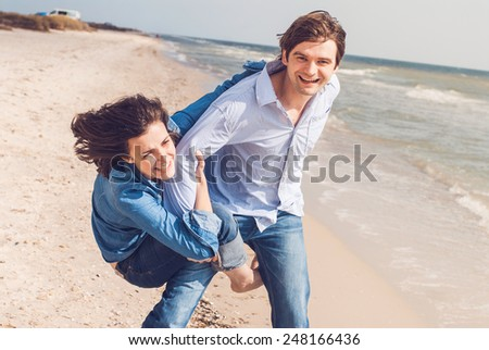 smiling young couple having fun on a summer beach - stock photo