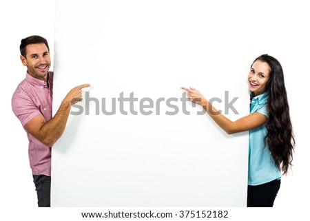 Smiling young couple holding white sheet on white screen - stock photo