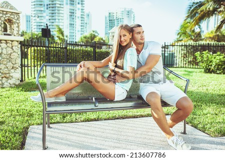 smiling young couple in love siting on bench at the park. - stock photo