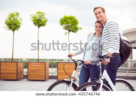 Smiling young couple looking at camera - stock photo