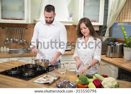 Smiling young couple preparing lunch together in the kitchen. Woman is cutting fresh vegetables and man is standing next to her and cooking on the stove. - stock photo
