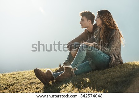 Smiling young couple sitting on grass during a sunny day, looking away and dreaming about their future - stock photo
