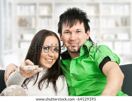 Smiling young couple sitting on sofa and watching TV - stock photo