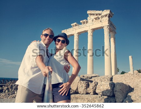 Smiling young couple take a selfie photo on antique ruins. Temple of Apollo, Side, Turkey - stock photo