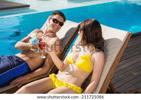 Smiling young couple toasting drinks by swimming pool - stock photo