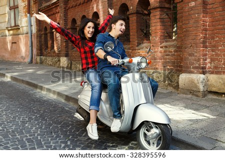 Smiling young couple, wearing in shirts and jeans, riding on the vintage scooter in old European city, with brick building on a background, full body  - stock photo