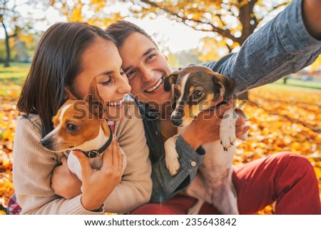Smiling young couple with dogs outdoors in autumn park making selfie - stock photo