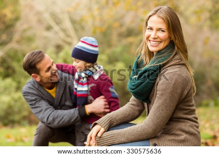 Smiling young couple with little boy posing on an autumns day - stock photo