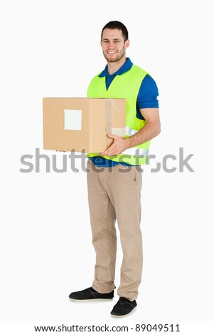 Smiling young delivery man holding a parcel against a white background - stock photo