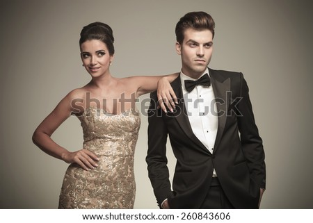 Smiling young elegant woman leaning on her lover, both looking away from the camera. - stock photo