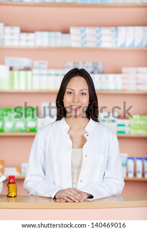 smiling young employee standing behind pharmacies counter - stock photo