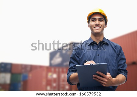 Smiling young engineer in protective work wear in shipping yard examining cargo - stock photo