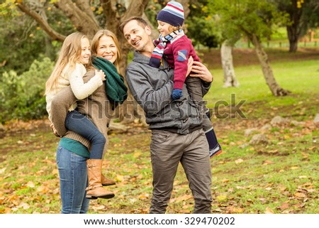 Smiling young family looking each other on an autumns day