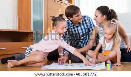 Smiling young family of four playing at board game at home