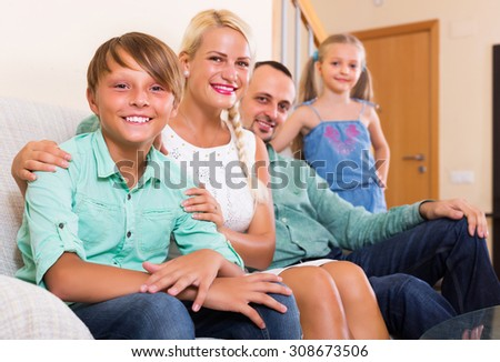 Smiling young family with two kids on couch indoors - stock photo