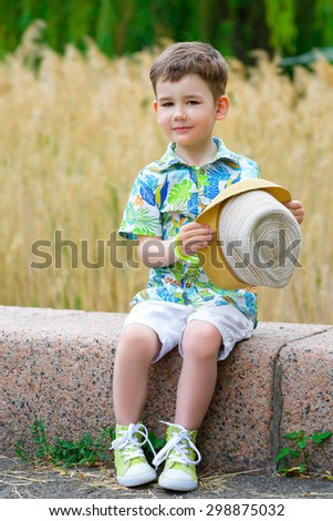 Smiling young fashion boy holding his hat while looking down, posing - stock photo