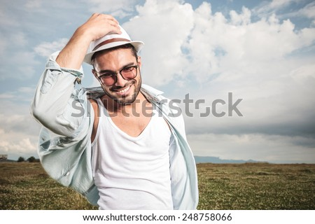Smiling young fashion man holding his hat while looking down, posing on a field full of flowers. - stock photo