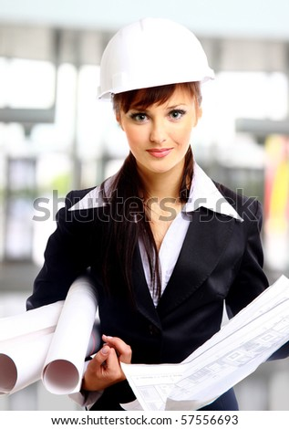Smiling young female architect holding blueprints isolated on white background - stock photo