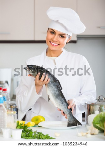 Smiling young female cook preparing big fish with lemon and herbs in restaurant kitchen