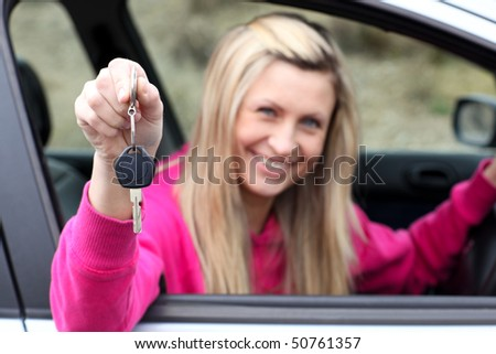 Smiling young female driver showing a key after buying a new car - stock photo
