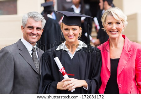 smiling young female graduate with parents at graduation ceremony - stock photo