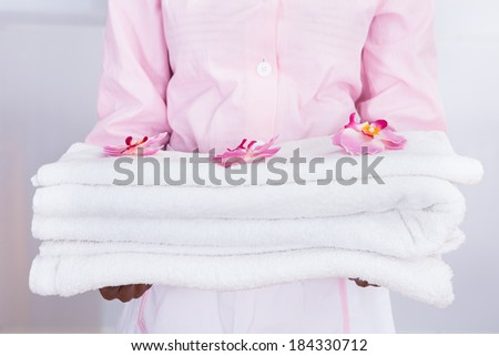 Smiling young female housekeeper carrying towels in hotel - stock photo