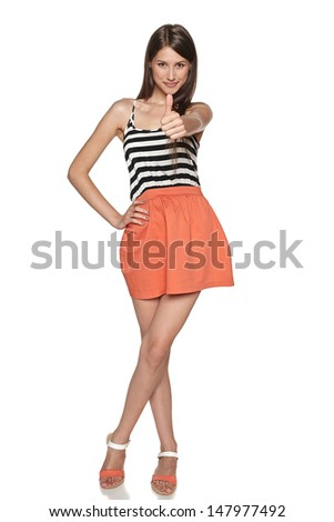 Smiling young female in full length showing thumb up gesture, over white background - stock photo