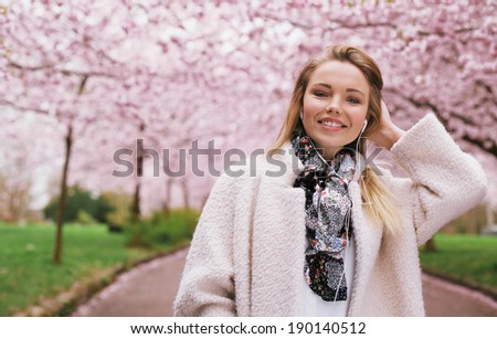 Smiling young female model wearing earphones while at park. Pretty woman wearing coat at spring blossom park. Caucasian woman outdoors with copy space. - stock photo