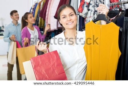 Smiling young female shopper chooses liked things in the boutique