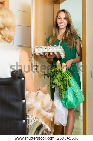 Smiling young female social worker bringing food to invalid's home - stock photo