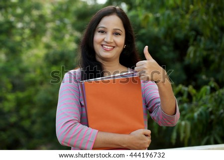 Smiling young female student making thumb up gesture - stock photo