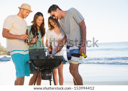 Smiling young friends having barbecue together on the beach - stock photo