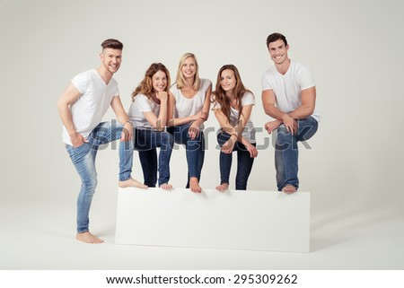 Smiling Young Friends in Casual White Shirts and Blue Jeans, Leaning their Feet on Empty White Board with Copy Space on Off-White Background Inside the Studio. - stock photo