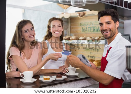 Smiling young friends with woman holding out credit card at the coffee shop - stock photo