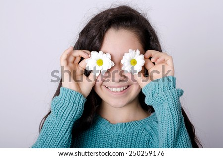 Smiling Young Girl Covering her eyes with Flowers - stock photo