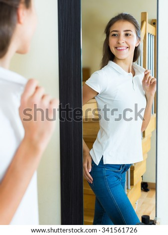 Smiling young girl dresses up in front of a mirror at home